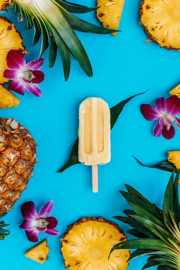 Tropical flatlay with vegan popsicle with various fruits and flowers around on blue by Nataly Lavrenkova on 500px.com