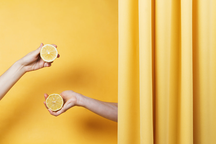 Two women's hands holding cut lemons on yellow, selective focus by Nataly Lavrenkova on 500px.com