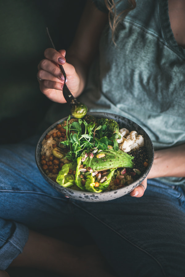 Woman sitting and eating healthy vegan dish from bowl by Anna Ivanova on 500px.com