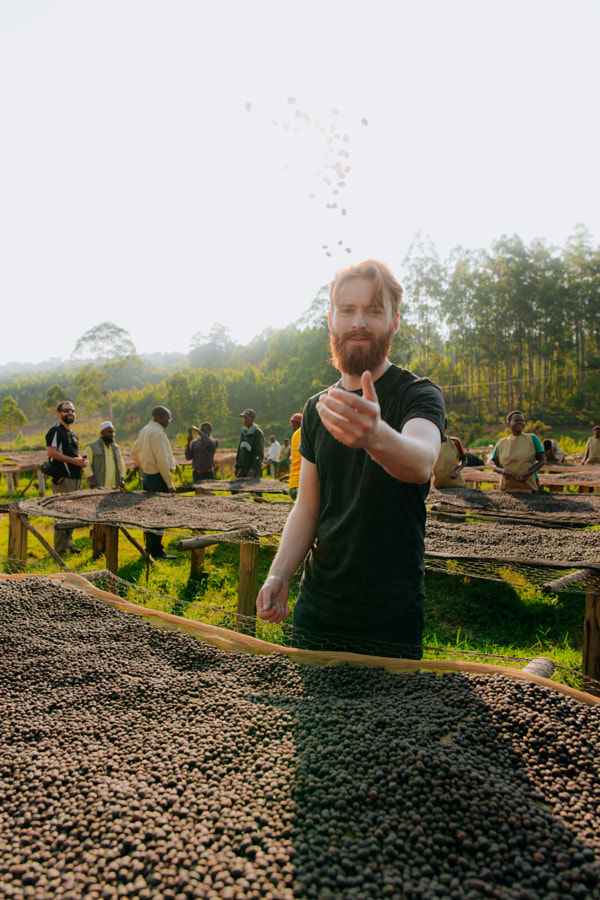 Man throwing coffee beans in the air in Rwanda by Aidan Campbell on 500px.com