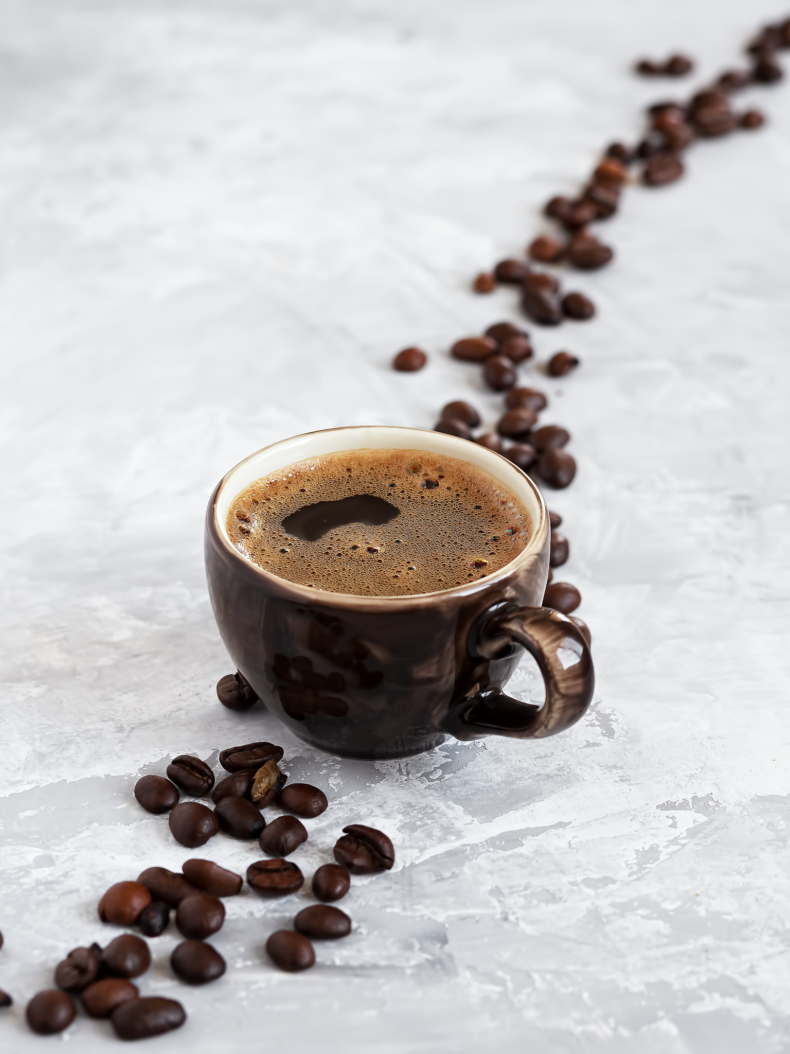 Cup with dark espresso arranged on a gray background. Roasted coffee beans are located around a cup