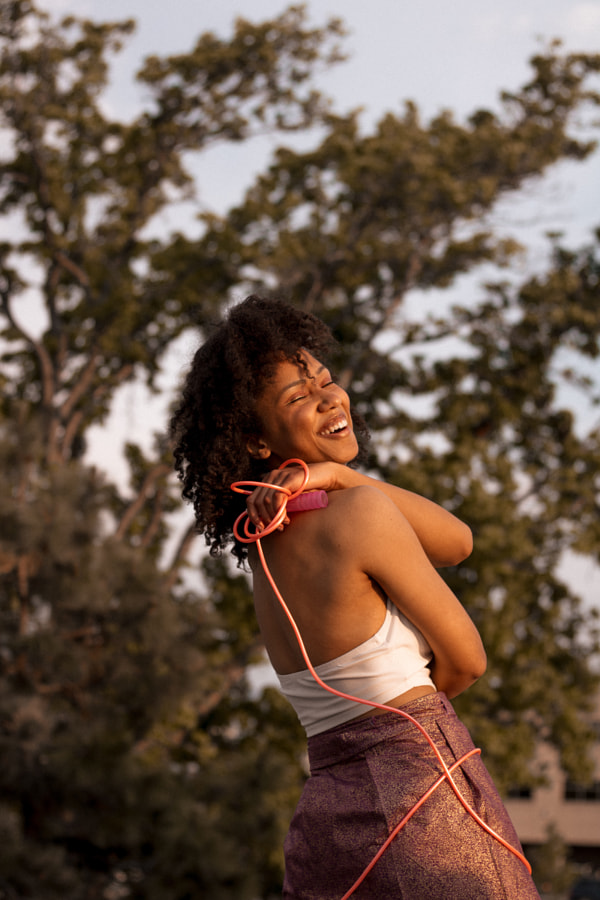 Young African American girl laughing outdoors with arms and rope around body by Hagar Wirba on 500px.com
