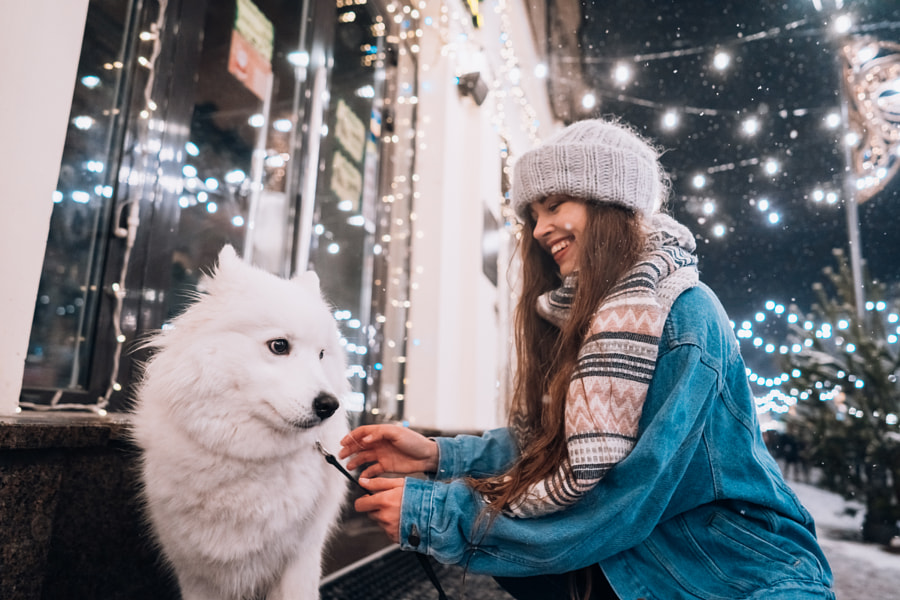 A young woman crouched beside a dog on a winter street. by Oleksii Hrecheniuk on 500px.com