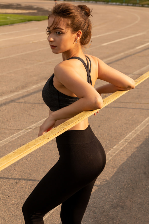 Young sexy athletic girl standing on a stadium