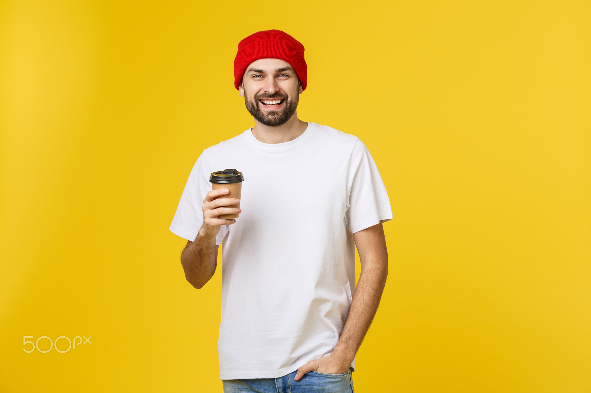 Man on isolated vibrant yellow color taking a coffee in takeaway paper cup and smiling because he wi