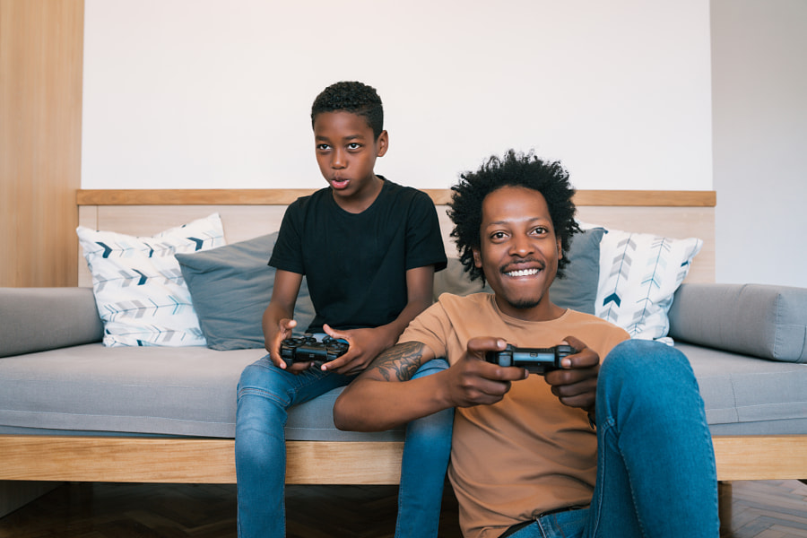 happy African American father and son playing console video games by Mego Studio on 500px.com