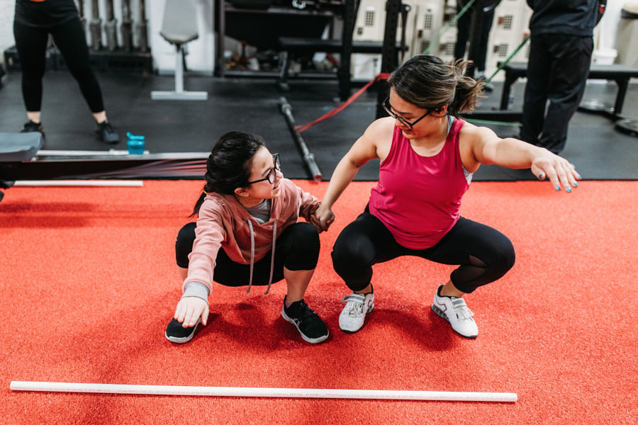 Asian female weightlifter showing daughter how to lift, Sharlene by Winnie Bruce on 500px.com
