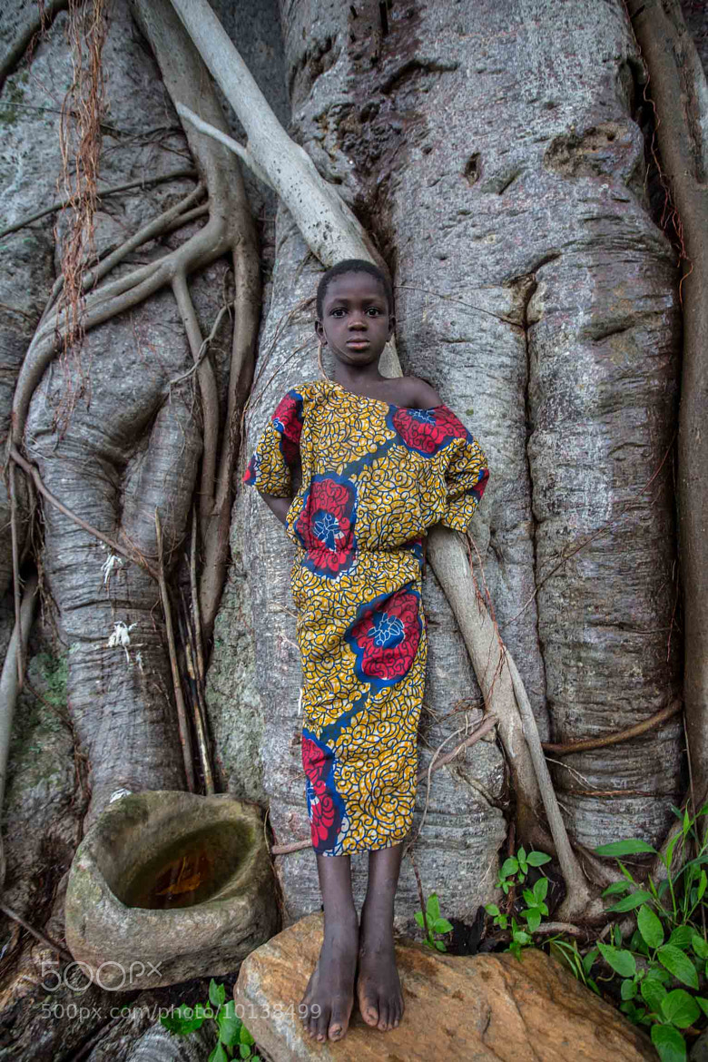 Photograph portrait of a taneka girl leaning against the baobab tree in the valley Atakora by Anthony Pappone on 500px