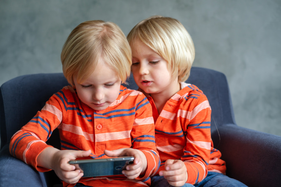 Brothers are watching or playing or learning something in a smartphone by ????? ????????? on 500px.com