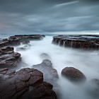 A few months ago, I discovered a fantastic seascape photography location on the NSW south coast, which appears not to have been visited by many photographers in the photographic communities of which I am a part.  I have visited this location twice -- first with seascaping buddies Sonia, Steve, Malcolm and Don -- and again today. The sky was terrible during my first visit (and I was not happy with the images), but this morning it was moody and produced much better results.  I am very surprised that this location has apparently not been photographed much. I only know of a few people who have been there, yet is is so accessible, dramatic and powerful.  In my opinion, it rivals and even exceeds many of the prime seascaping locations on Sydney's Northern Beaches, with big gorges, splashes and cascades aplenty.  This rock shelf features many striking features, and is only a few minutes' walk north from the ocean pool on the northern rock shelf at Kiama.  It is well worth visiting, and while the place can produce huge seas, there is plenty of space for retreating, and it is not as isolated as other rock shelves along the coast.  If you haven't been yet, I thoroughly recommend this location. There is a lot to shoot, and plenty of drama when the big sets of waves roll in.  Here is a short video I produced, showing the fantastic main gorge and cascading, churning water:  http://www.youtube.com/watch?v=BRo84xVqXI0
