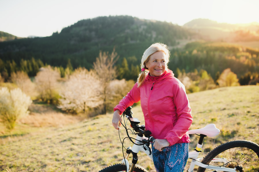 Active senior woman with bicycle outdoors in nature, resting. by Jozef Polc on 500px.com