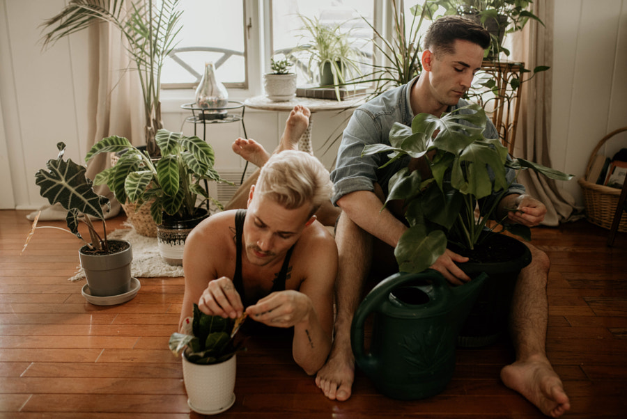 Two adult LGBTQ+ men caring for their houseplants by Kyle Kuhlman on 500px.com