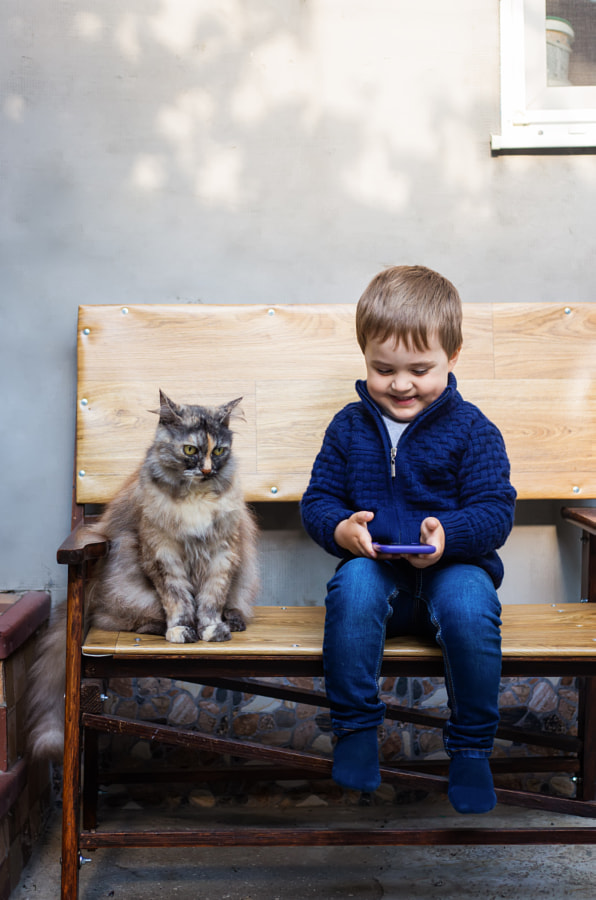 Little boy looking at a mobile phone with a cat by Oleksandra Mykhailutsa on 500px.com