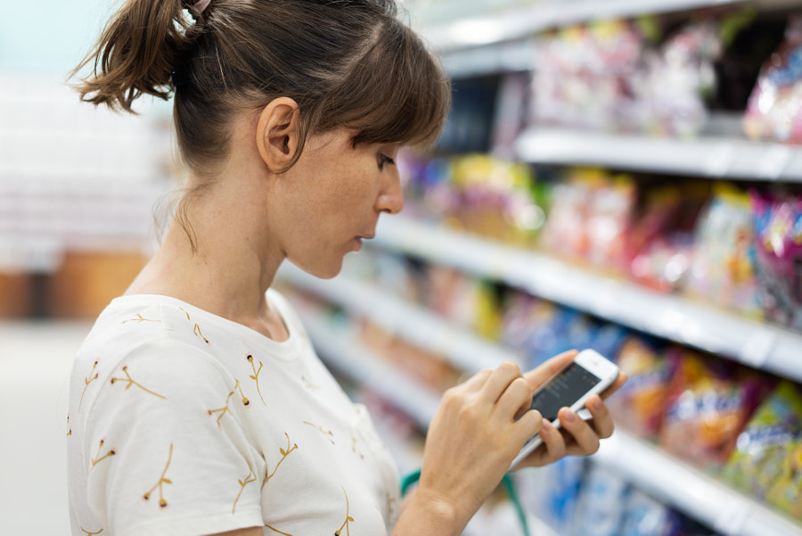 Woman in supermarket checking shopping list on smartphone by Oleksandr Boiko on 500px.com
