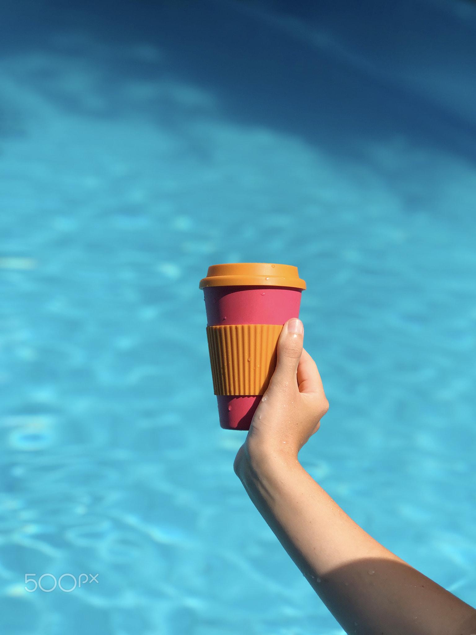 Woman enjoying coffee in a reusable bamboo mug at the swimming pool