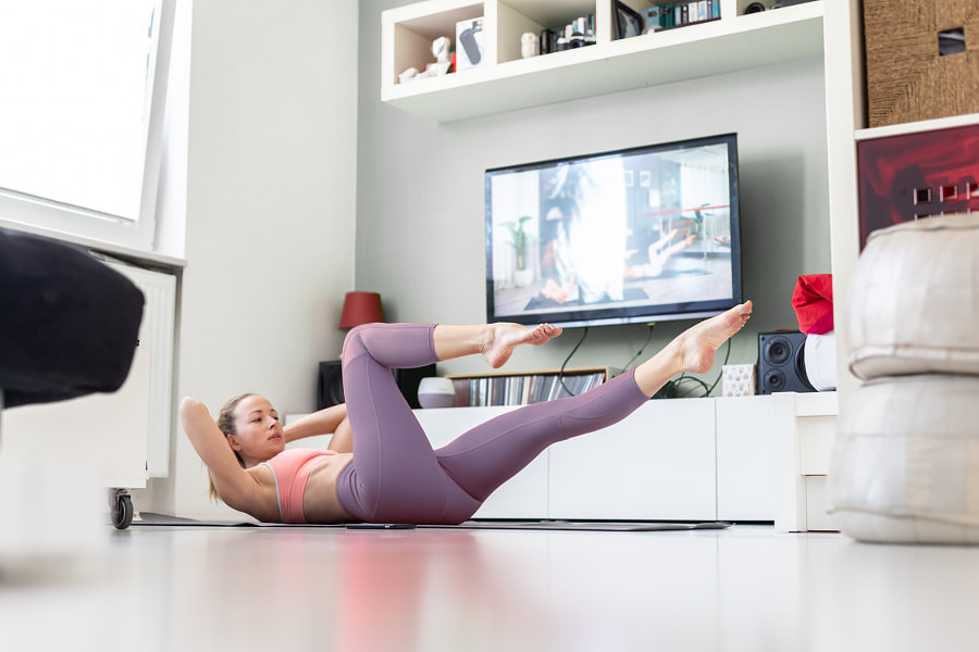Attractive sporty woman working out at home, doing pilates exercise in by Matej Kastelic on 500px.com