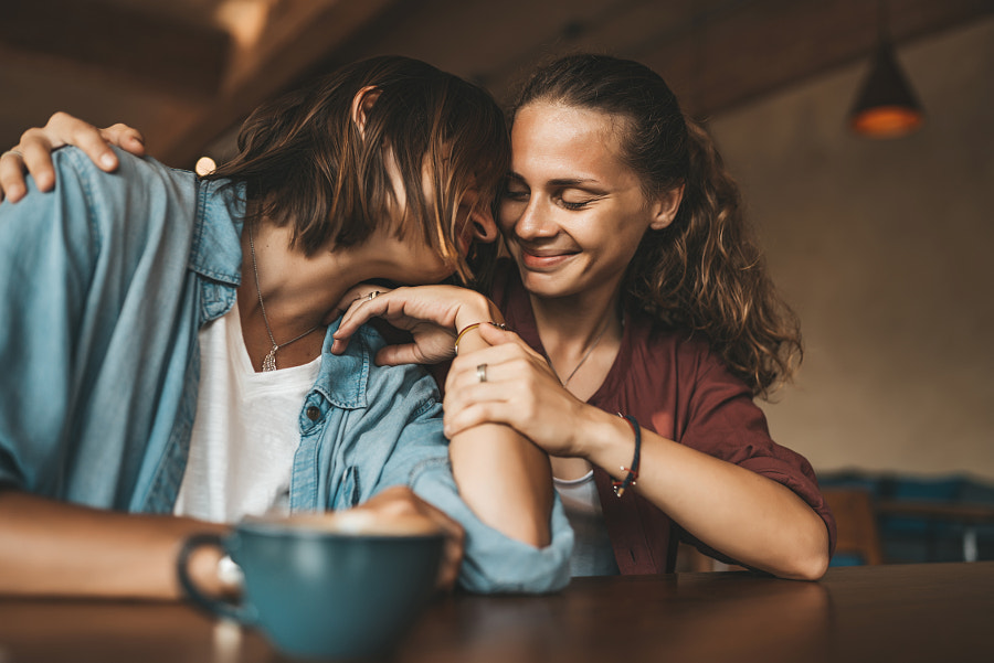 Lesbian couple hugging in cafe by Natalie Zotova on 500px.com