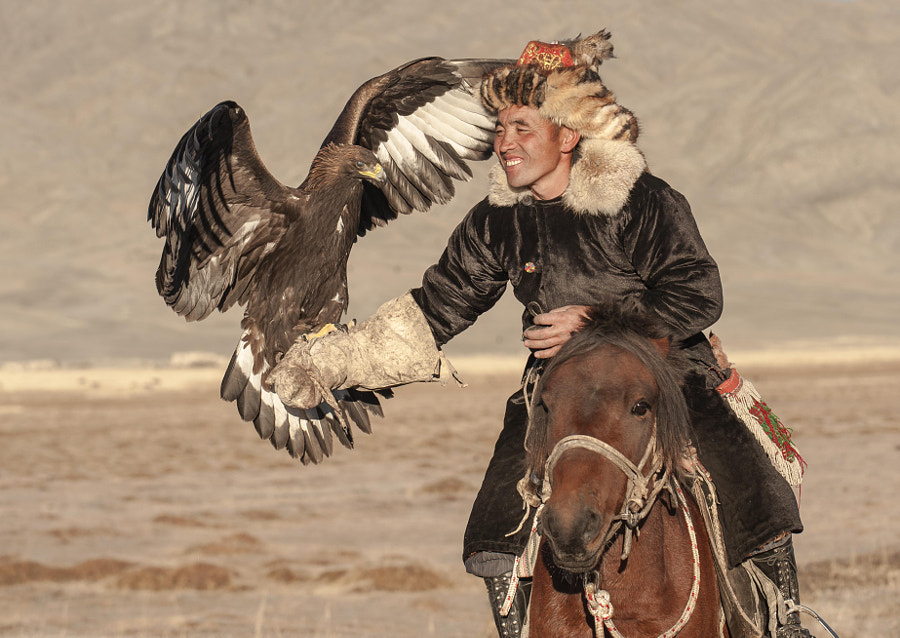 golden eagle landing on kazakh eagle hunter arm by Kevin Pepper on 500px.com