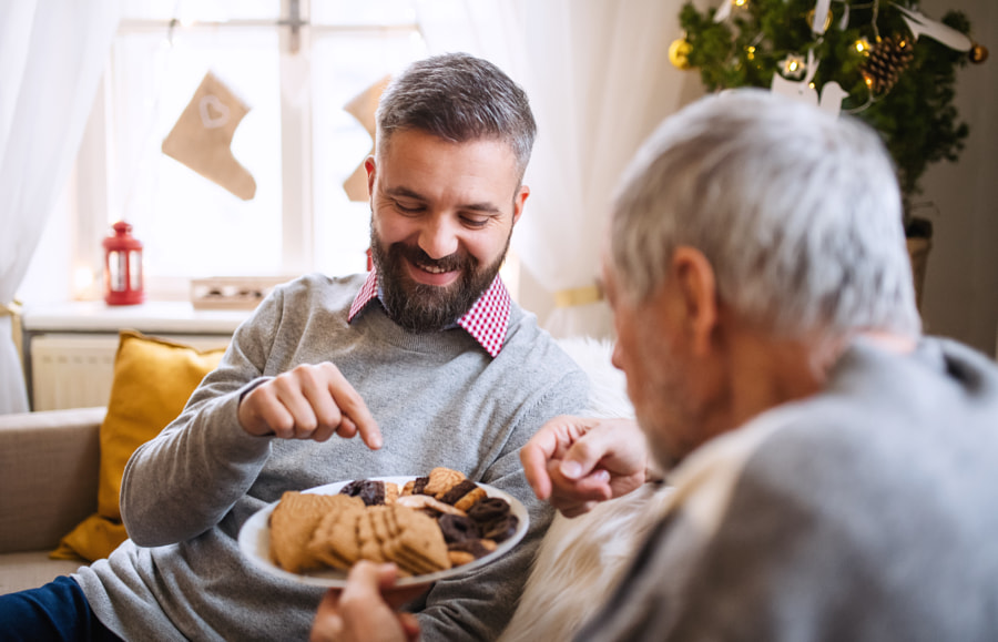 Mature man and senior father indoors at home at Christmas, eating by Jozef Polc on 500px.com
