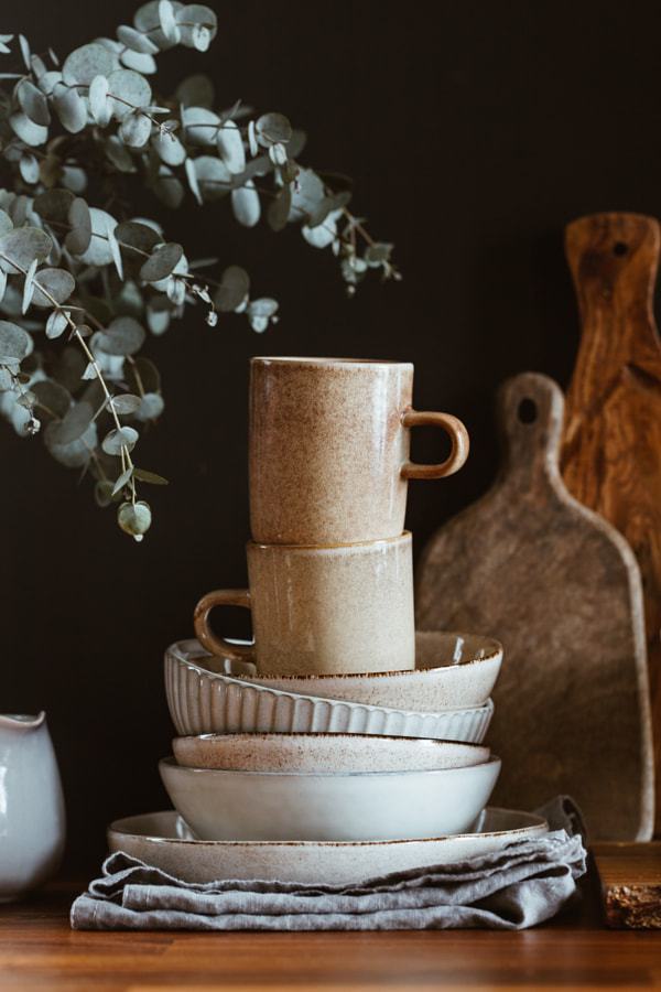 Set of kitchen ceramic tableware and wooden cutting boards on a table by Edalin Photography on 500px.com