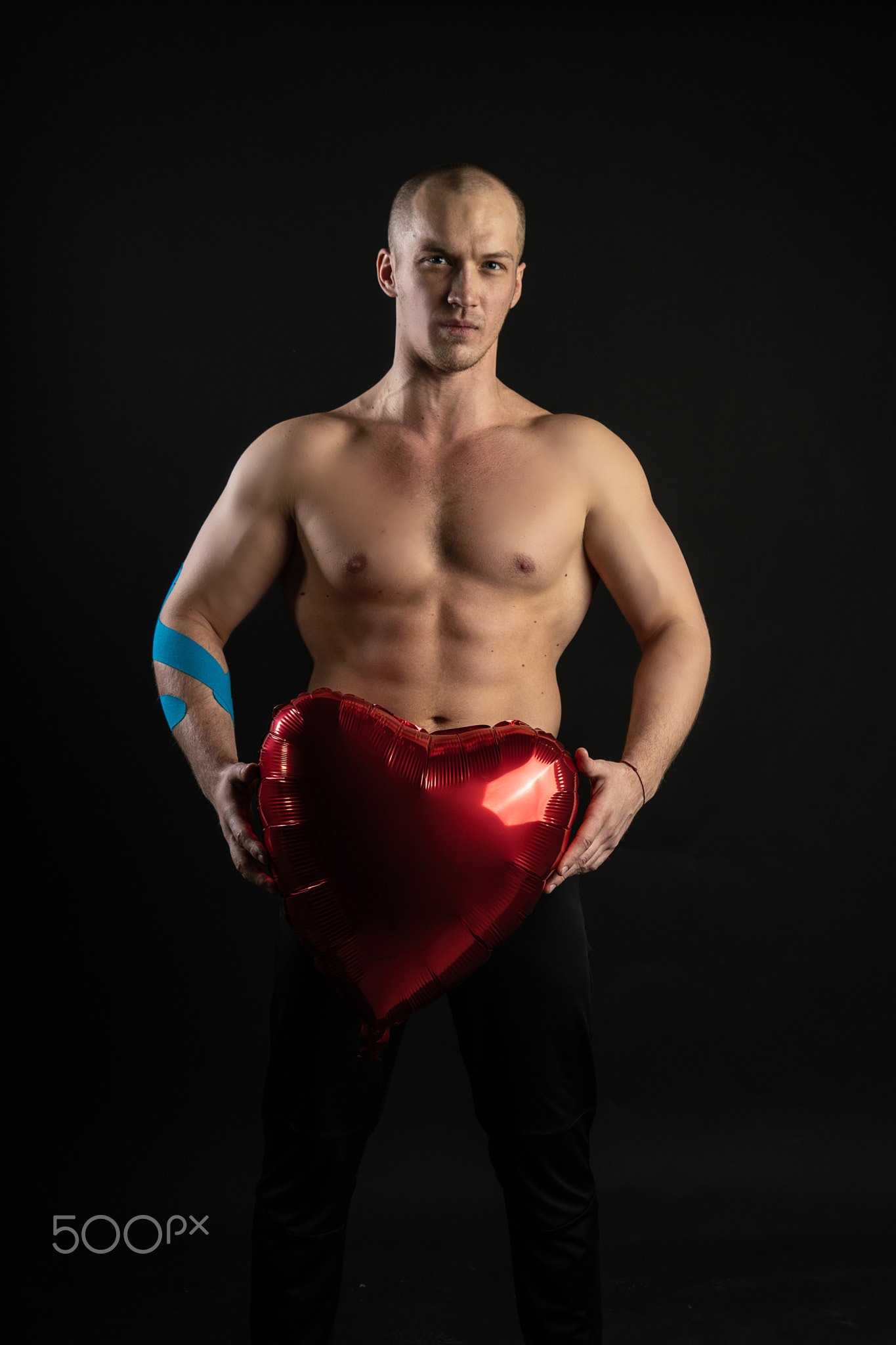 Athletic man holding a red heart, a naked balloon in his hand for a