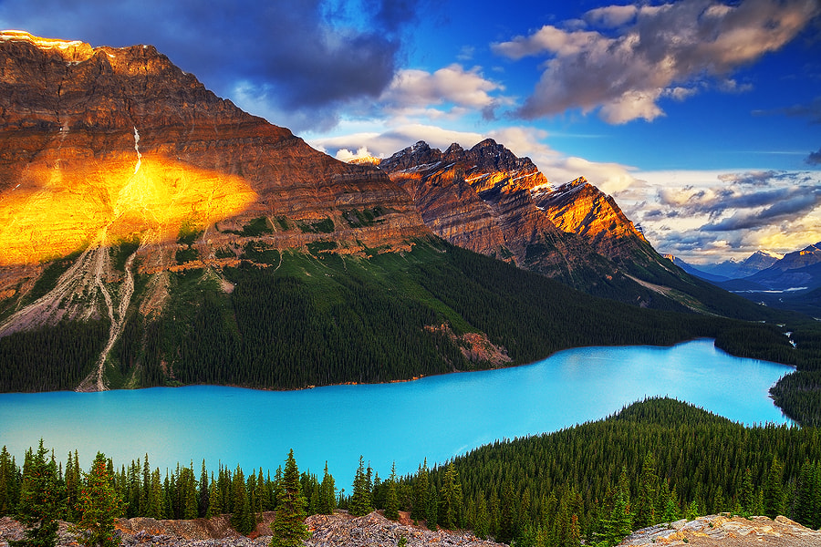 First sun rays hit Caldron Peak and Mount Patterson above magnificent Peyto lake, Alberta, Canada