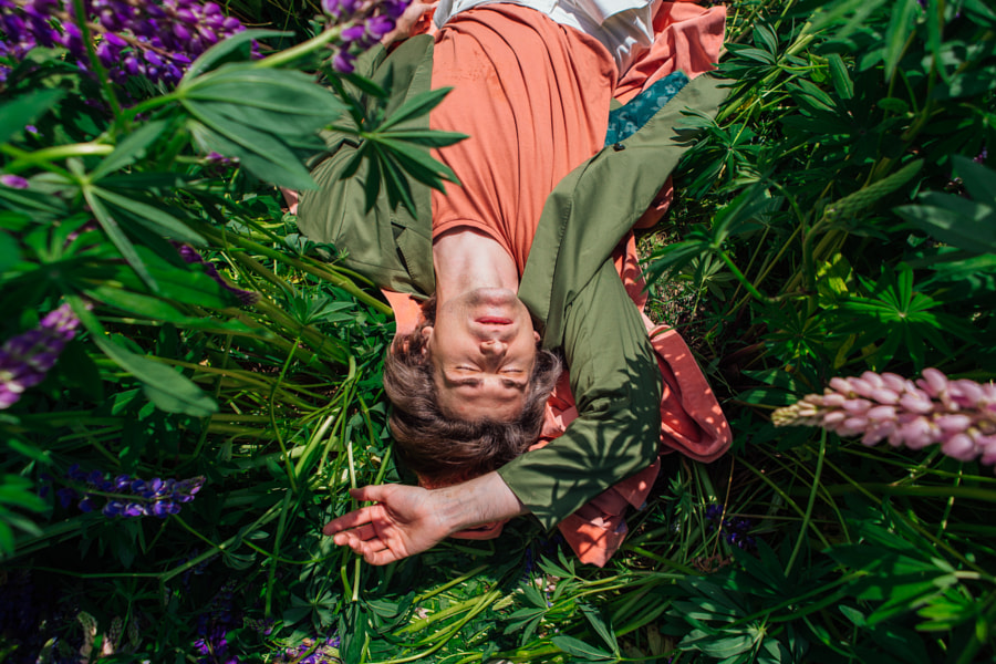 Young handsome man lies in lupins by Elena Yurkina on 500px.com