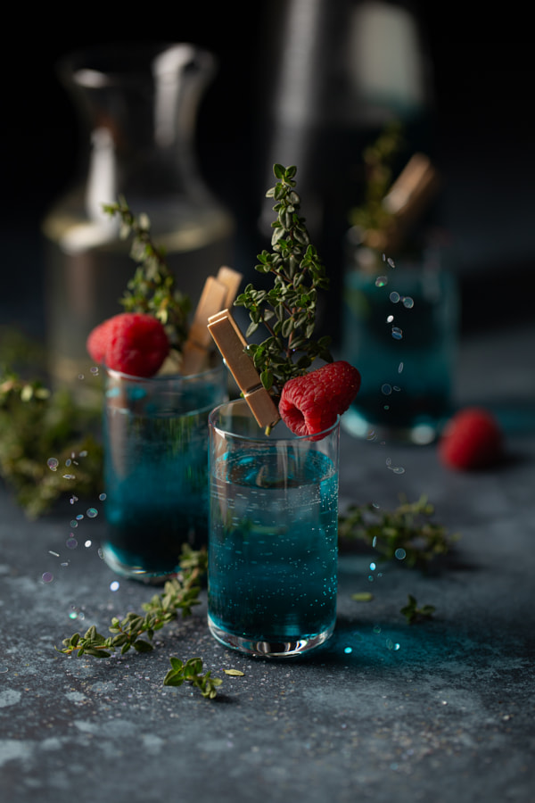 Set of cocktails in shot glasses with blue liqueur,thyme sprigs and by Olga  on 500px.com