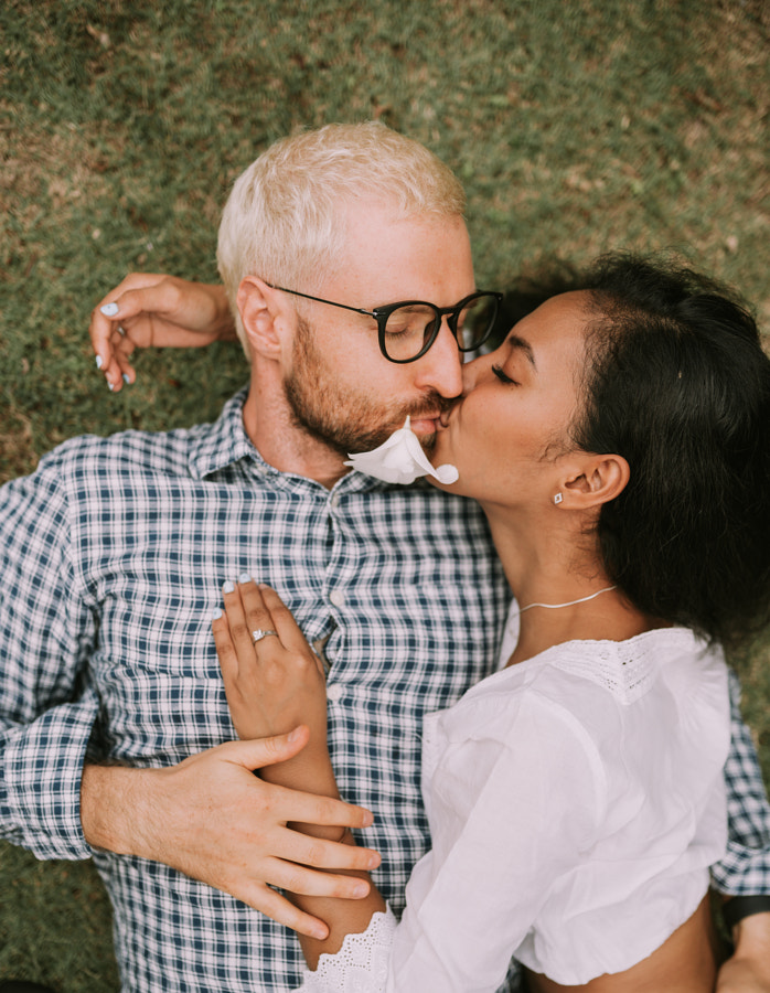 Multinational couple of asian woman and blonde man laying on the grass by Natalie Zotova on 500px.com