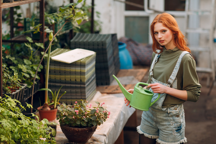 Home gardening concept. Young ginger girl with watering can plants by Max Chernishev on 500px.com