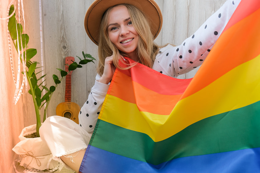 Young blonde woman with rainbow LGBTQ flag at home. Peace and freedom by Anastasiia Yanishevska on 500px.com