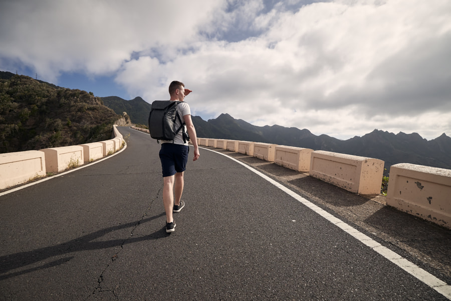 Rear view of man with backpack on mountain road by Jaromír Chalabala on 500px.com