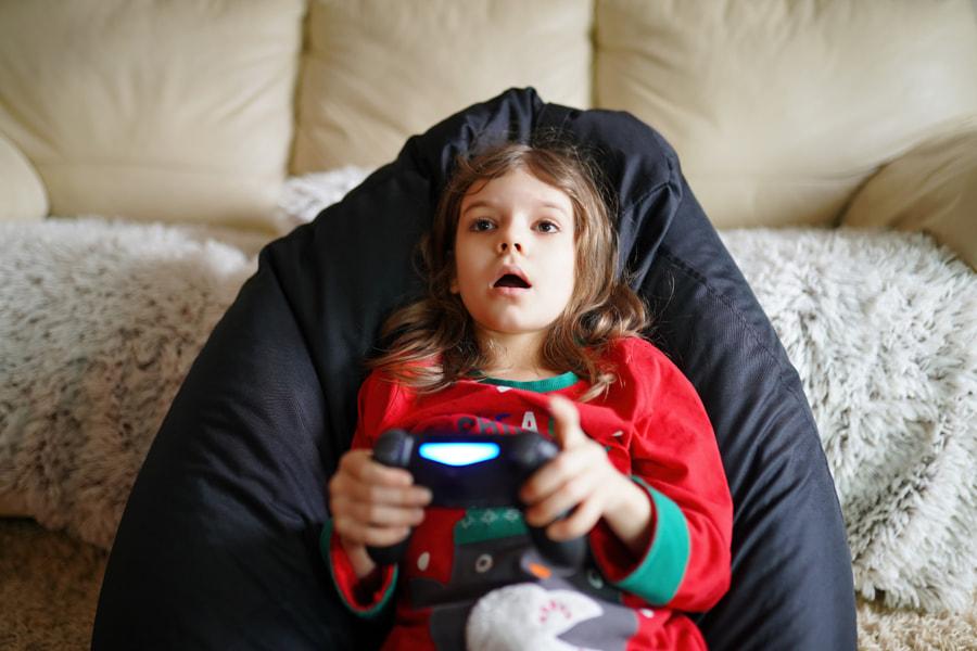 Gamer girl playing gamepad, joystick in games on big screen by Aleksandr Zamuruev on 500px.com