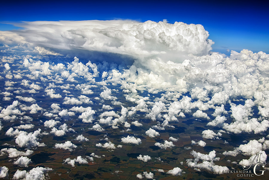 One big cumulonimbus cloud and whole army of supporting popcorn above the Argentinian pampas from the altitude of 11 kilometers