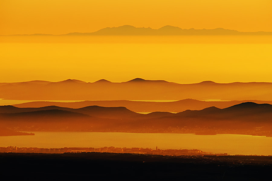 At sunset, from Velebit mountain, view spreads over 40km distant Zadar city and parallel layers of Zadar archipelago islands all the away across the Adriatic sea to the Apennines mountains, a spine of Italian boot, some 270km away...