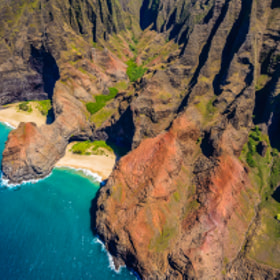 View of Honopu Valley and 90 foot natural arch from a helicopter over Kauai, Hawaii