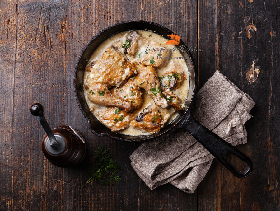 Roasted chicken with creamy garlic sauce in cast iron frying pan