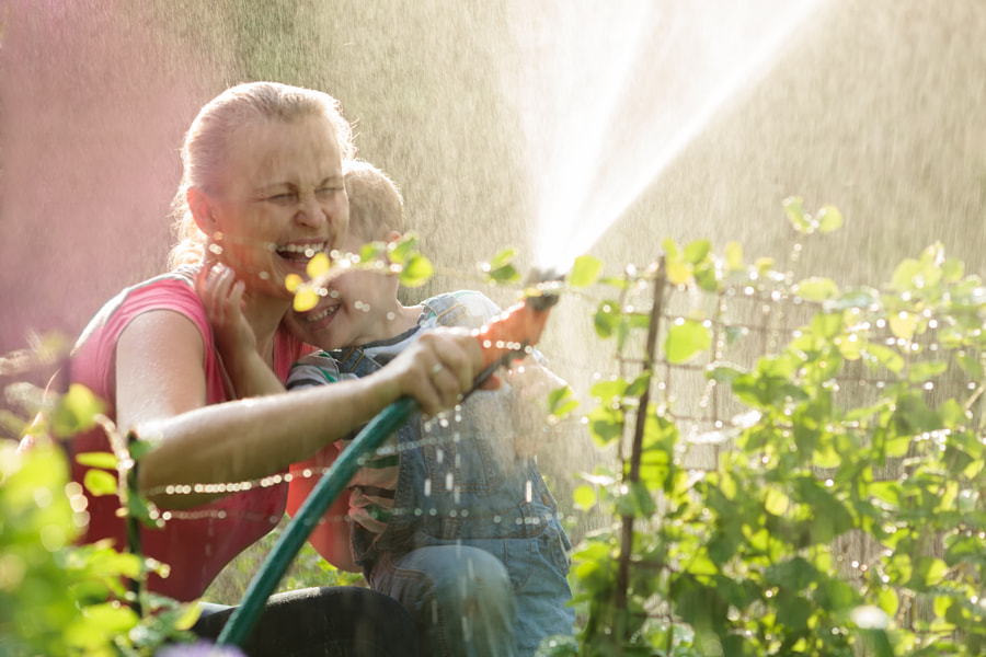 Laughing mother and son playing with a sprinkler by Danil Roudenko on 500px.com