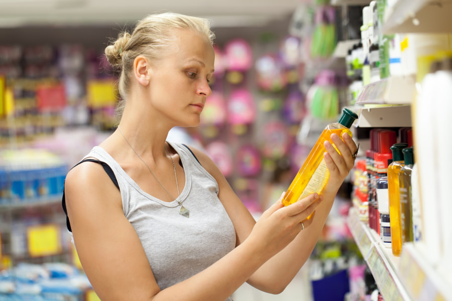 Woman looking at shampoo bottle in the store by Danil Roudenko on 500px.com