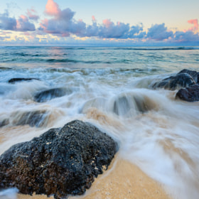 Waves crashing over rocks just after sunrise in Poipu, Kauai