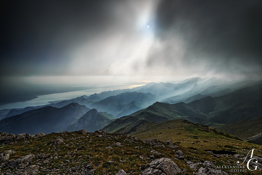 A moment of fantastic and strange mystique on the summit of Sveto Brdo (1751m), just below the gliding Bura wind cloud, with a view towards peaks and valleys of the Paklenica area wrapped in mist and Adriatic sea at the back