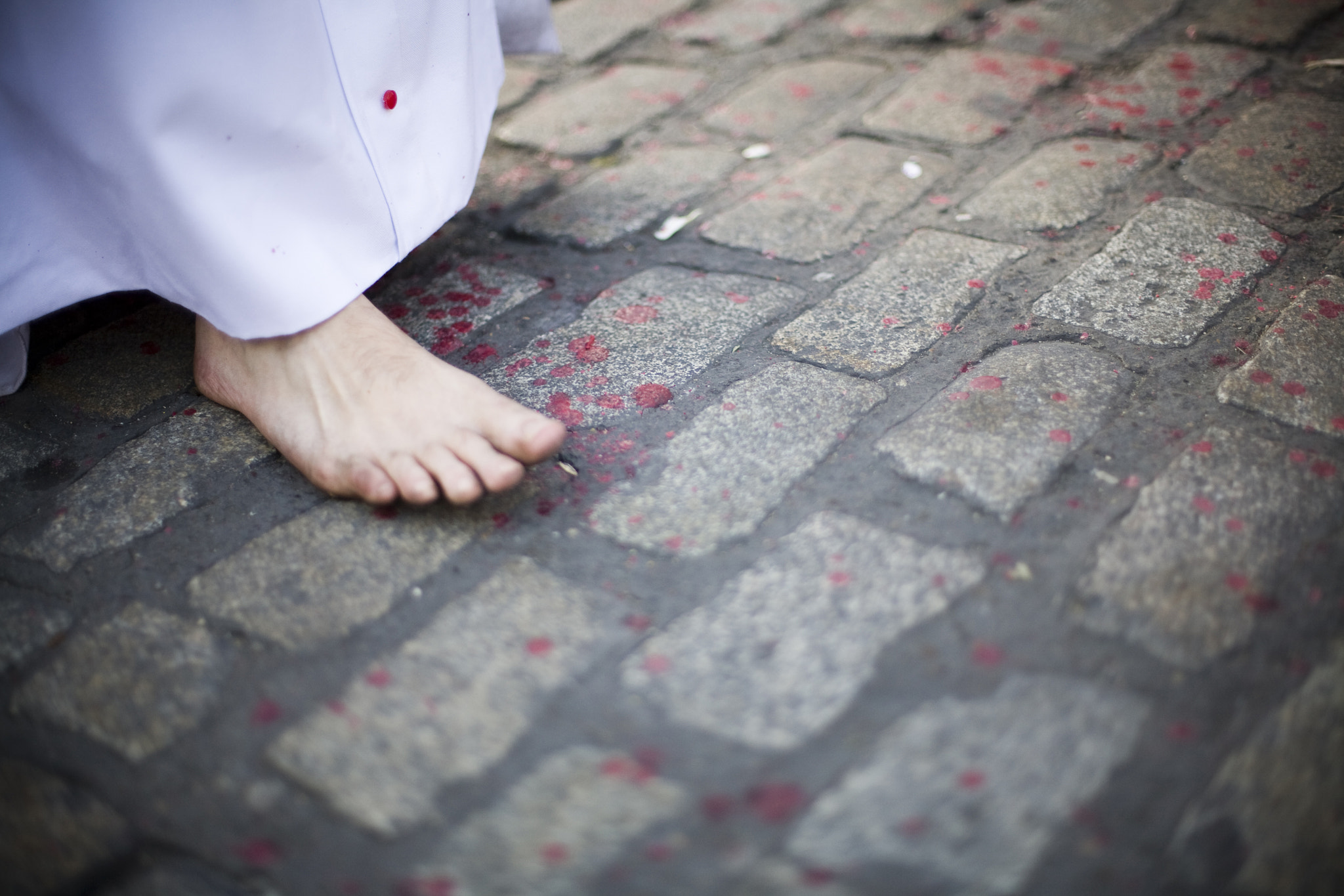 Detail of a barefoot penitent walking on the pavement with melted wax drops, Holy Week 2008, Seville