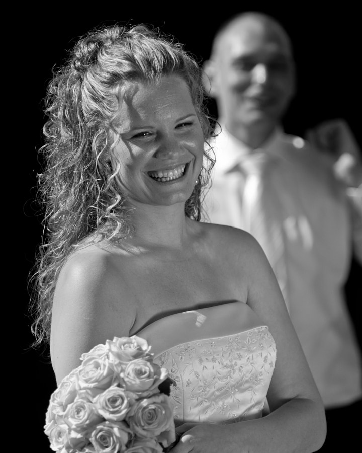 Smiling bride in front of groom