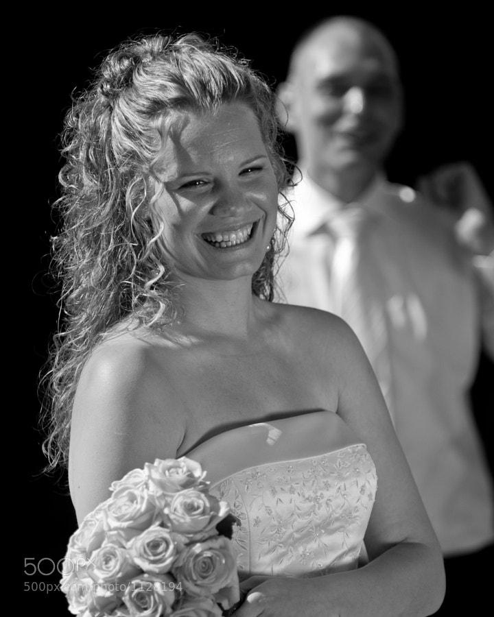 Smiling bride in front of groom