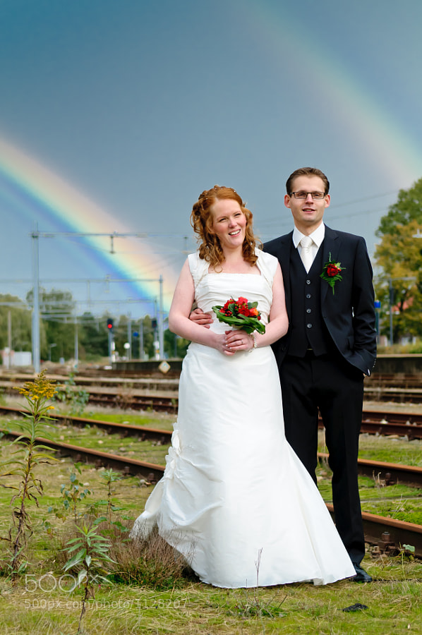 Bride and groom between train rails with two rainbows in the background.