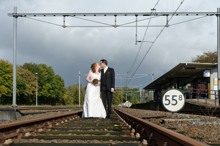 Bride and groom between train rails at station Coevorden, Drenthe (Netherlands)