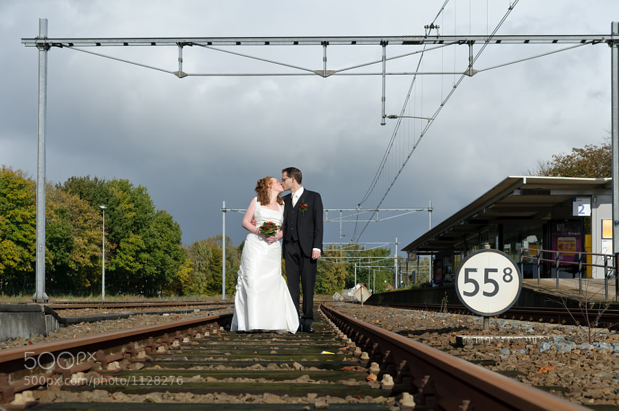 Bride and groom between train rails at station Coevorden, Drenthe (Netherlands)
