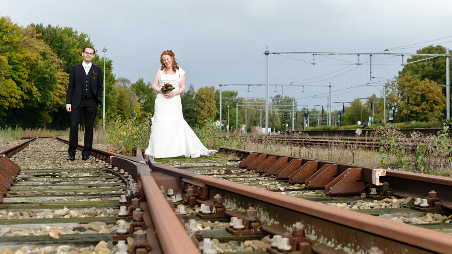 Bride and groom between trail rails at station Coevorden, Drenthe (Netherlands)