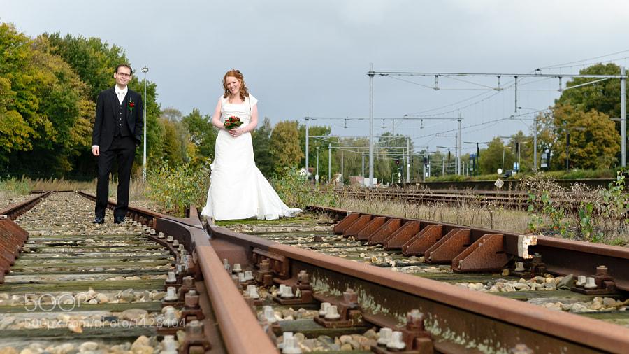 Bride and groom between trail rails at station Coevorden, Drenthe (Netherlands)