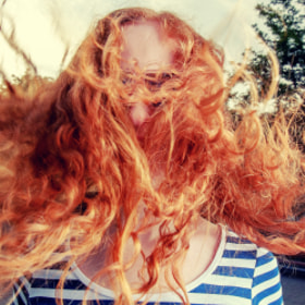Portrait of a beautiful redhead girl with flying hair in the wind outdoors.